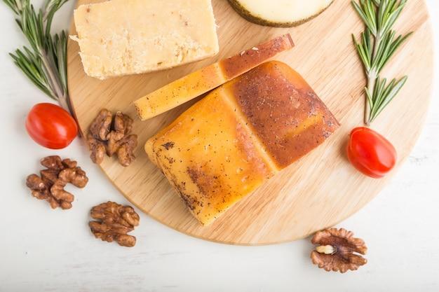 Fromage fumé et divers types de fromage au romarin et tomates sur planche de bois sur une surface en bois blanc