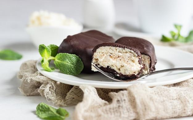 Fromage glacé en grains avec du chocolat et de la menthe et une tasse de café.