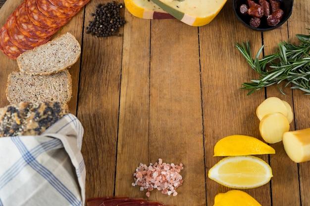 Fromage gouda, citron vert doux, viande, tranches de pain, poivre noir et romarin sur planche de bois