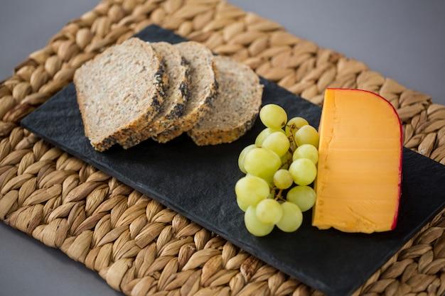 Fromage gouda, tranches de pain et raisins sur plaque d'ardoise
