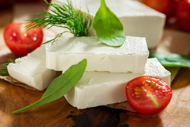Fromage grec feta à l'aneth et tomates cerises sur une planche à découper en gros plan