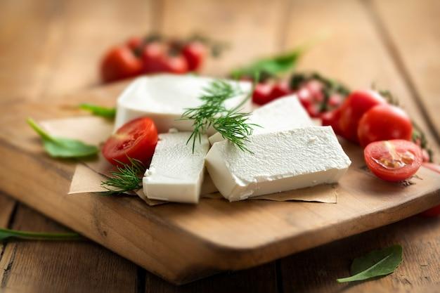 Fromage grec feta à l'aneth et tomates cerises sur planche à découper