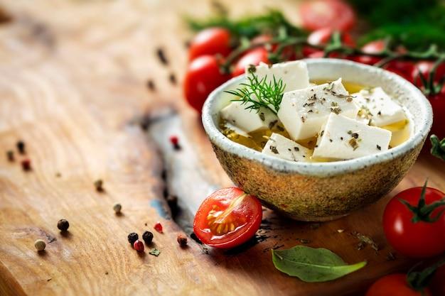 Fromage grec feta avec huile d'olive et olives, aneth et tomates cerises sur planche à découper, espace pour copie