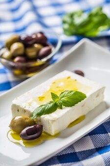 Fromage grec feta avec olives à l'huile d'olive et feuilles de basilic.