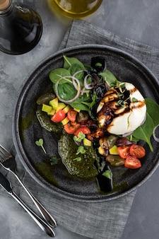 Fromage italien frais burrata avec pesto de sauce et légumes. bouteilles avec sauce, nappe grise, cuillère et fourchette. face à la grande fenêtre du restaurant. vue de dessus