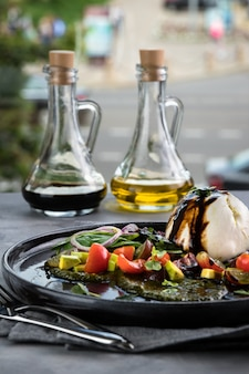 Fromage italien frais burrata avec pesto de sauce et légumes. bouteilles avec sauce, nappe grise, cuillère et fourchette. face à la grande fenêtre du restaurant