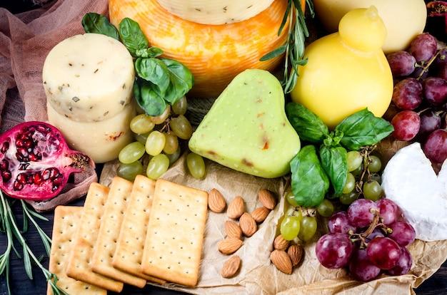 Fromage maison assorti de différentes sortes avec des légumes, des fruits, des biscuits et des noix sur la table. produits laitiers frais, aliments biologiques sains. délicieux apéritif.