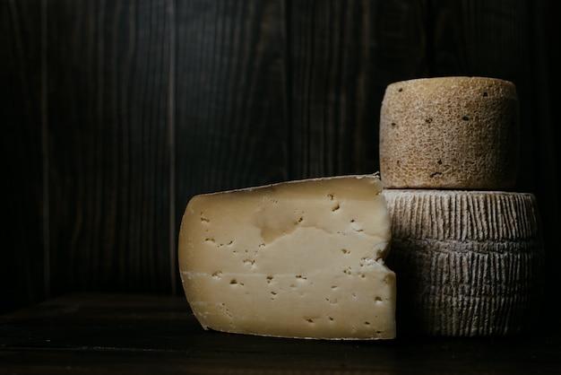 Fromage manchego à côté de gorgonzola et kravot sur une planche de bois sombre. photographie de fromages en discret. fromage à pâte molle naturel à base de lait de vache et de chèvre