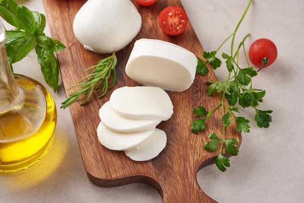 Fromage mozzarella frais, fromages italiens à pâte molle, tomate et basilic, huile d'olives et romarin sur planche de service en bois sur une surface en bois clair. la nourriture saine. vue de dessus. mise à plat.