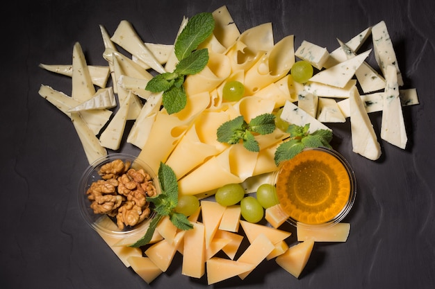 Fromage, noix et miel assortis, décorés des raisins et des feuilles de menthe sur une table noire