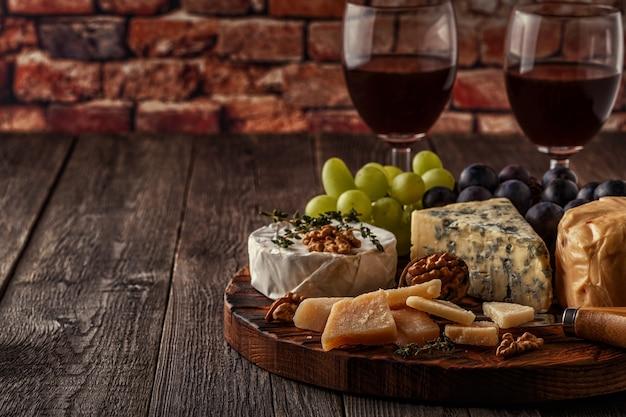 Fromage, noix, raisins et vin rouge sur fond de bois