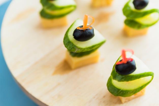 Fromage, olive et concombre sur une brochette en plastique sur une planche à découper
