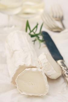 Fromage sur papier blanc et verre de vin blanc