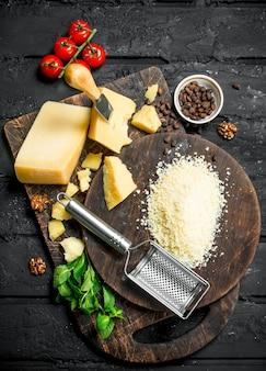 Fromage parmesan râpé aux pignons de pin, tomates et herbes. sur noir rustique.