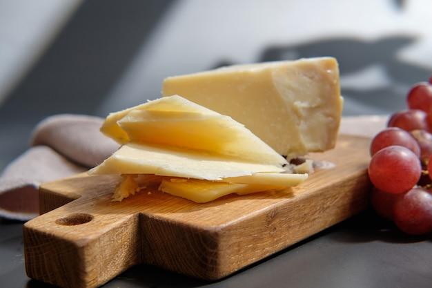 Fromage parmigiano sur une planche en bois avec des baies de raisin