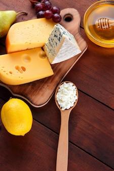 Fromage à pâte dure, fromage bleu et fromage cottage sur planche de bois.