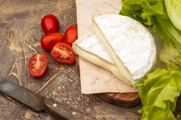 Fromage à pâte molle avec de la moisissure blanche sur une planche à découper, avec des légumes. fermer
