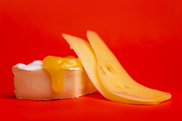 Fromage à pâte molle avec moisissure et fromage à pâte dure sur fond rouge.