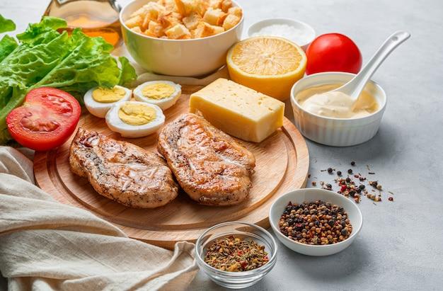 Fromage de poitrine de poulet juteuse oeufs laitue et tomates sur une planche à découper sur un bureau gris