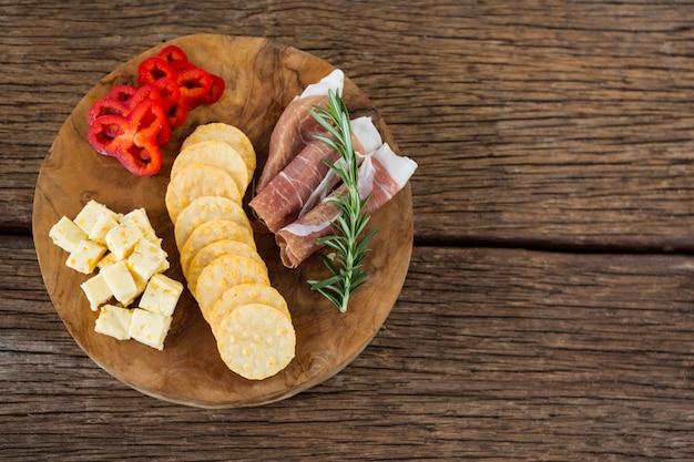 Fromage, poivrons rouges, viande et croustilles nacho sur table en bois