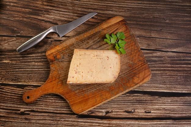 Fromage à raclette au piment sur une planche à découper en bois sur une table en bois