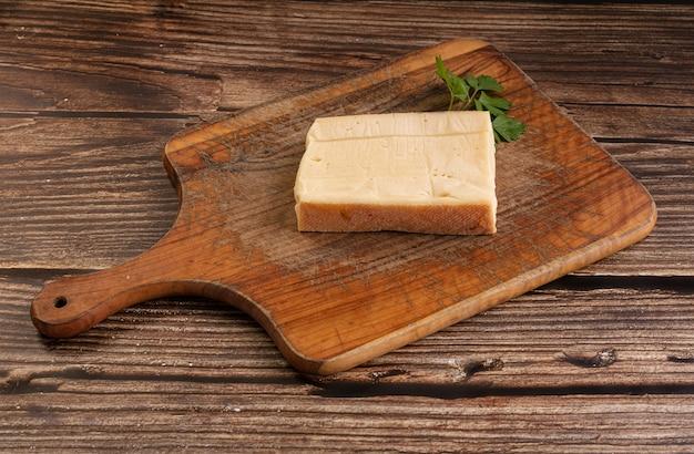 Fromage à raclette nature sur une planche à découper sur une table en bois