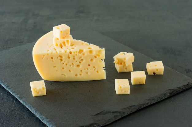 Fromage radamer sur fond de béton noir. morceau triangulaire de fromage suisse au lait de vache jaune avec des trous.