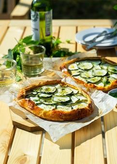 Fromage recette italienne et galette de zuccini servis à l'extérieur sur une table de jardin avec du vin blanc.
