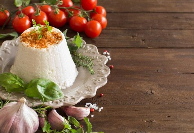 Fromage ricotta italien, légumes et herbes sur une table en bois se bouchent
