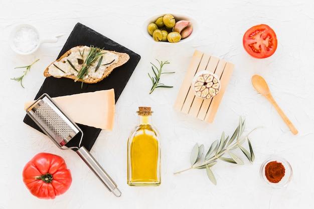 Fromage et romarin sur pain aux olives et tomates sur fond blanc