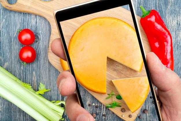 Fromage rond frais sur l'écran du smartphone.