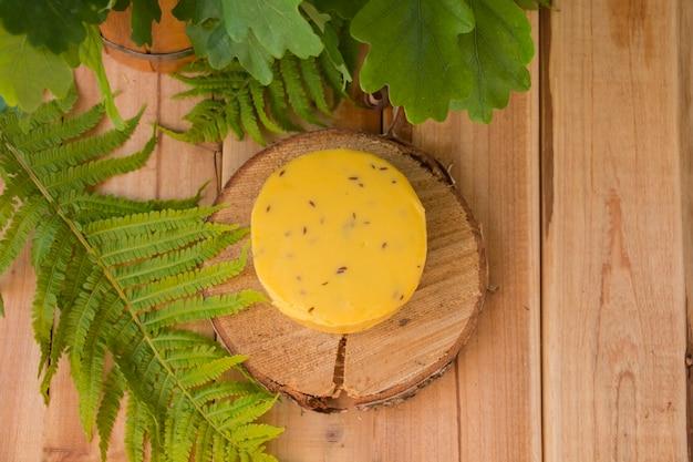 Fromage rond traditionnel aux graines de carvi sur une assiette en bois avec des feuilles autour