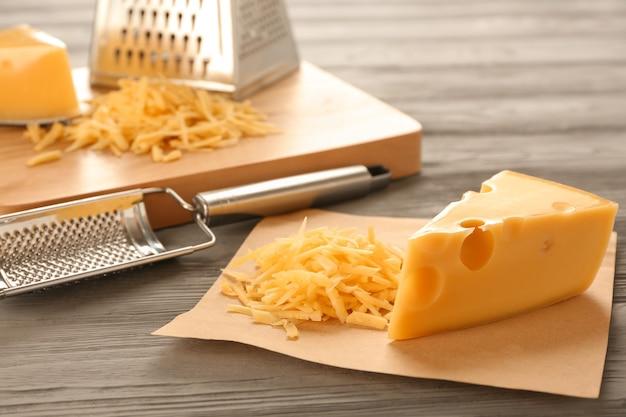Fromage savoureux et râpes sur table en bois