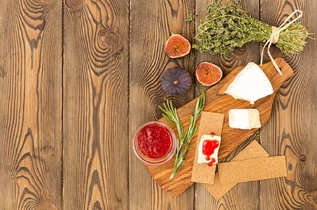 Fromage servi avec de la confiture, des figues, des craquelins et des herbes sur un fond en bois.