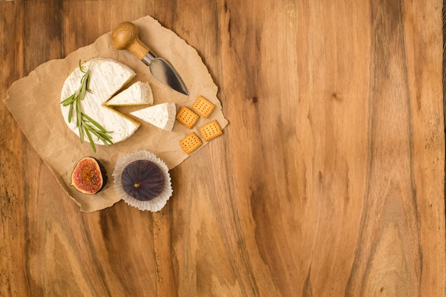 Fromage servi avec des figues, des craquelins et des herbes sur un fond en bois.