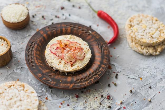 Fromage et tranches de navet sur un gâteau de riz soufflé sur le fond de béton