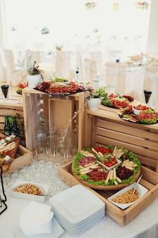 Le fromage en tranches et la viande sont servis sur un plat avec des olives sur des boîtes en bois
