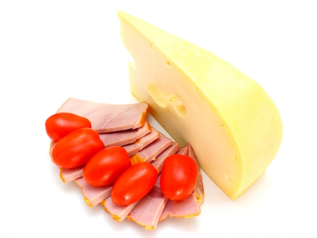 Fromage avec des trous et des tomates rouges se trouvent