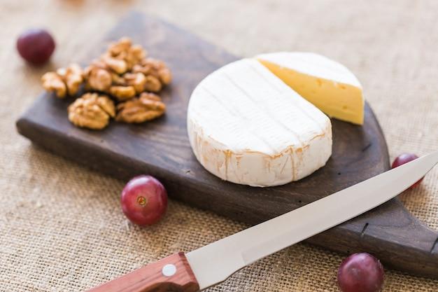 Fromage de type brie. le camembert. fromage brie frais sur une planche de bois avec des noix et des raisins. fromage italien, français.