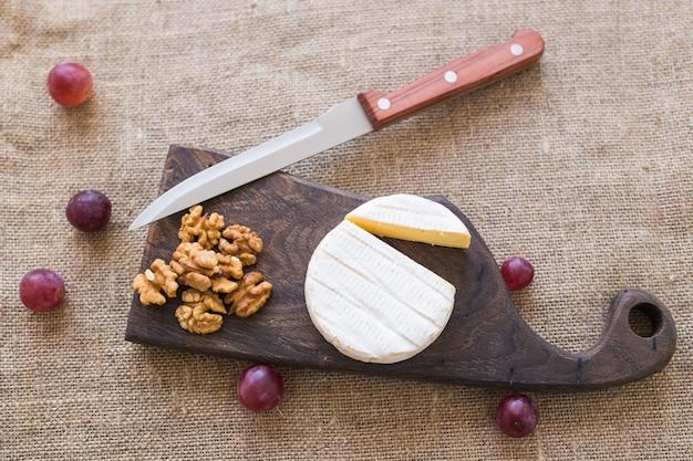 Fromage de type brie. le camembert. fromage brie frais sur une planche de bois avec des noix et des raisins. vue de dessus de fromage italien, français.