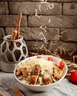 Fromage verser sur la salade caezar vue latérale