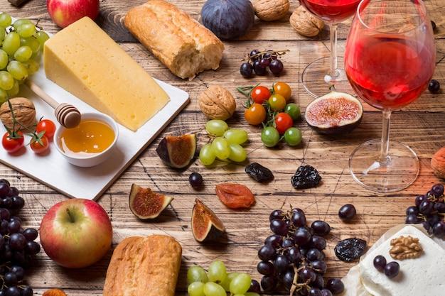Fromage, vin, baguette, figues, raisins, miel et collations sur le plateau en bois rustique.