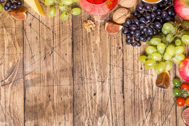 Fromage, vin, baguette, figues, raisins, miel et collations sur le plateau de table en bois rustique avec espace de copie.