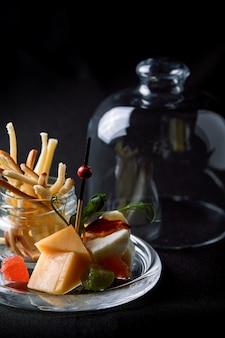 Fromages assortis aux fruits rouges et marmelade, mini-service dans une fiole en verre. concept de cuisine fusion, discret, espace copie.