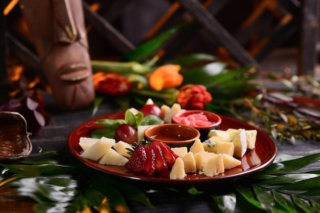 Fromages assortis avec fraises, raisins et sauce. dans une assiette rouge. avec décor floral