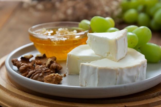 Fromages blancs et ronds sur bois avec du miel, des noix et des raisins.