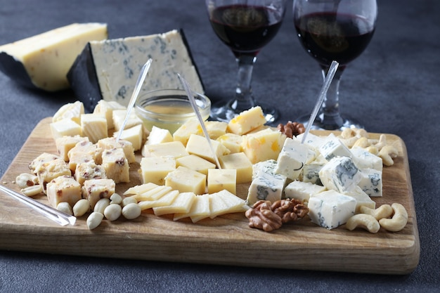 Fromages d'élite : à la truffe, dor bleu, brie, parmesan et assortiment de noix sur une planche en bois. apéritif pour une soirée vin