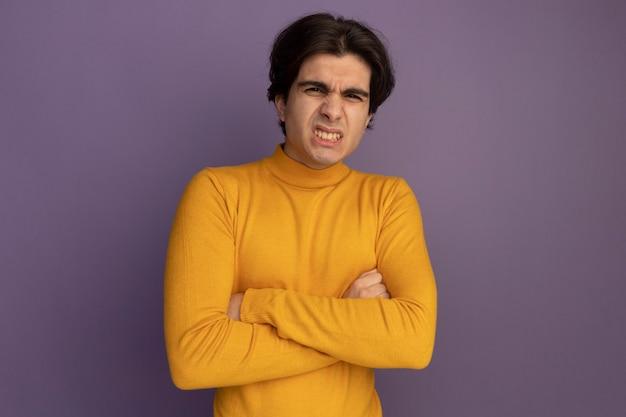 Fronçant les sourcils, beau jeune homme portant un pull à col roulé jaune croisant les mains isolées sur un mur violet