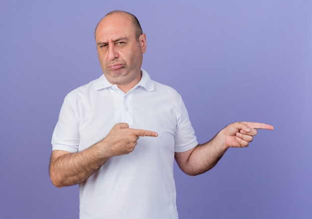 Fronçant les sourcils casual homme d'affaires mature regardant la caméra pointant sur le côté isolé sur fond violet