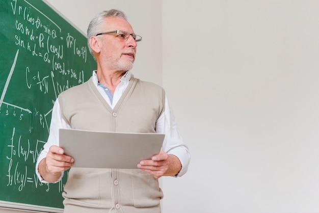 Fronçant les sourcils enseignant de mathématiques âgé avec des feuilles de papier